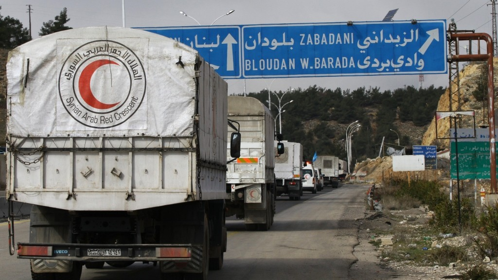A convoy of aid from the Syrian Arab Red Crescent heads to the besieged rebel-held Syrian town of Madaya, on January 14, 2016. The convoy of about 50 aid trucks left Damascus for the hunger-stricken Syrian town of Madaya where 40,000 residents have suffered a crippling government siege that has drawn sharp condemnation from the United Nations. / AFP / LOUAI BESHARA