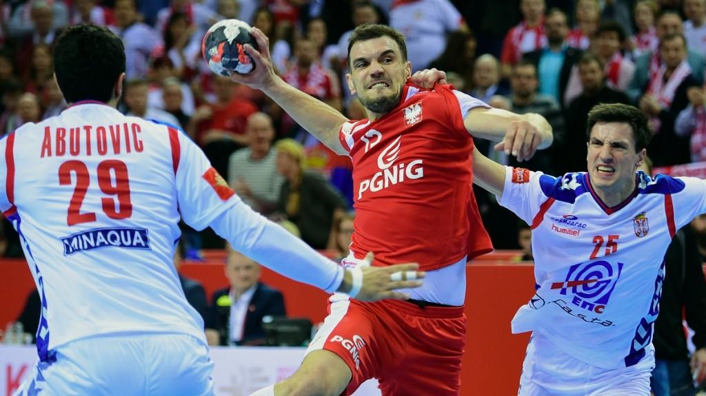 Micha? Jurecki (C) of Poland vies betveen Nemanja Zelenovi?  (R) and Ilija Abutovi? (L) of Serbia in Tauron Arena of Krakow on January 15, 2016 during their group 'A' match of the 'Men's EHF European Handball Championships 2016'.  Poland won 29-28.  / AFP / ATTILA KISBENEDEK