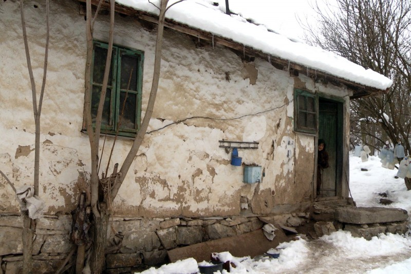 Marija Zlatic, 86, peeks out of her house in the remote mountainous area of the eastern Serbian town of Boljevac on January 21, 2016. A 86-year old hermit from eastern Serbia has become a millioner overnight being granted inheritance from Australia five years after her husband passed away. Following a years-long search by her neighbour, Marija Zlatic, who lives in a mud hut in a remote mountainous area of the eastern town of Boljevac, has received 940,000 Australian dollars (610,000 euros, $660,000), left behind her late husband Momcilo, who died in 2011, Vecernje Novosti daily reported.  / AFP / STRINGER