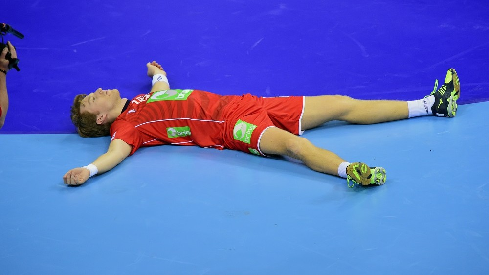 Kristian Bjørnsen of Norway lays in the hall after his team was defeated by Germany in the semi-final match of the Men's 2016 EHF European Handball Championship between Norway and Germany in Krakow on January 29, 2016. Germany won the match 33:34 after extra time and qualified for the final. / AFP / ATTILA KISBENEDEK
