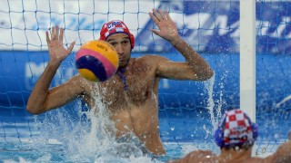 Croatia's goalkeeper, captain Josip Pavic (red) vies with the ball against Italy during the men's Water Polo European Championships quarter final match of Italy vs Croatia in Budapest on July 23, 2014.  AFP PHOTO / ATTILA KISBEN EDEK / AFP / ATTILA KISBENEDEK