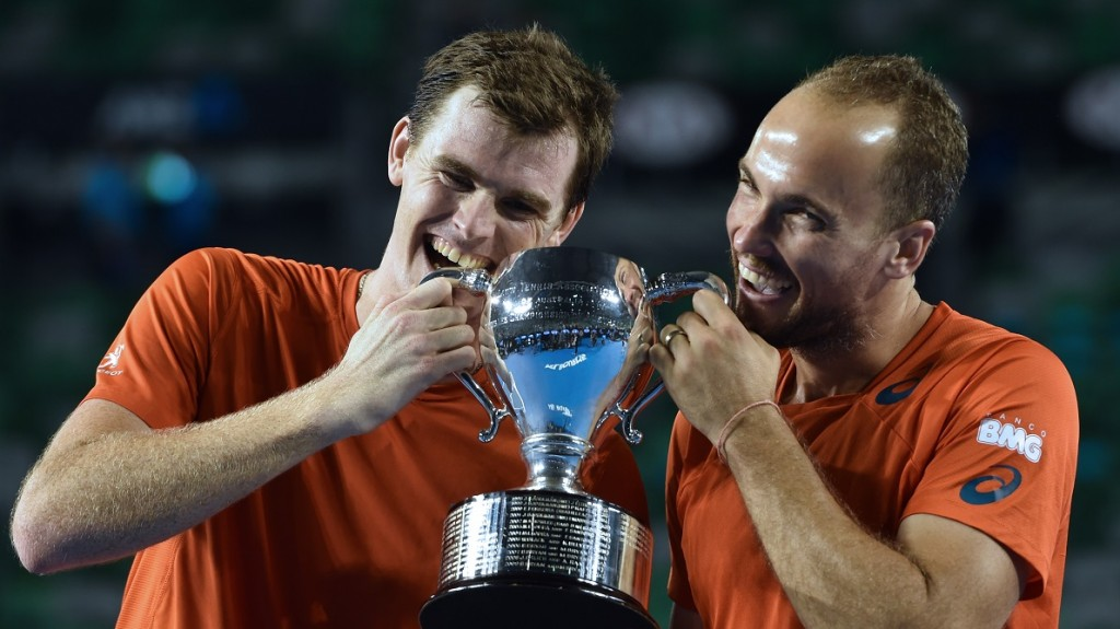 Britain's Jamie Murray (L) and Brazil's Bruno Soares pose with the trophy as they celebrate after victory in their men's doubles final match against Canada's Daniel Nestor and Czech Republic's Radek Stepanek on day thirteen of the 2016 Australian Open tennis tournament in Melbourne early January 31, 2016. AFP PHOTO / SAEED KHAN-- IMAGE RESTRICTED TO EDITORIAL USE - STRICTLY NO COMMERCIAL USE / AFP / SAEED KHAN