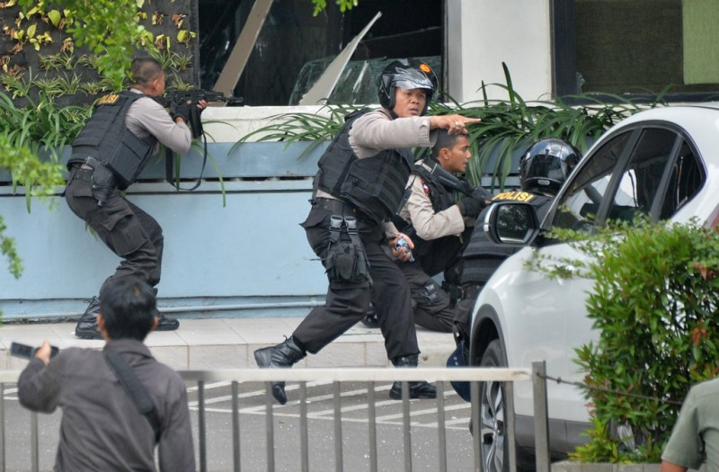 Indonesian police take position and aim their weapons as they pursue suspects outside a cafe after a series of blasts hit the Indonesia capital Jakarta on January 14, 2016. A series of bombs killed at least three people in the Indonesian capital Jakarta on January 14, with shots fired outside a cafe as police moved in, an AFP journalist at the scene said.     AFP PHOTO / Bay ISMOYO / AFP / BAY ISMOYO