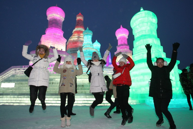 """Tourists celebrate in front of giant ice sculptures during the 32nd Harbin International Ice and Snow Festival in Harbin city, northeast China's Heilongjiang province, 5 January 2016.  The 2016 Harbin International Ice and Snow Festival kicked off in China's northeastern Heilongjiang province on Tuesday (5 January 2016), with large and intricate snow and ice sculptures on display. This year's festival is themed """"Pearl on the Crown of Ice and Snow"""". Over one million visitors are expected to attend the spectacular ice festival, where buildings of ice are bathed in ethereal lights and international ice sculptors compete for honours. The festival, which lasts three months, boasts more than 100 events, covering tourism, culture, trade, sports and fashion."""