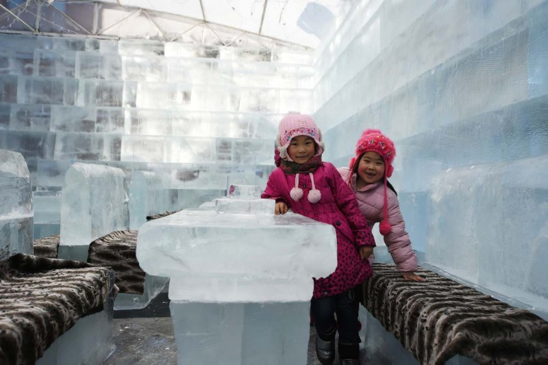 (160106) -- HARBIN, Jan. 6, 2016 (Xinhua) -- Young girls have fun in an ice bar in Harbin, capital of northeast China's Heilongjiang Province, Jan. 6, 2016. The ice bar,which occupied some 100 square meters, used ice to build all the bar counters, tables and benches. (Xinhua/Wang Jianwei) (cxy)