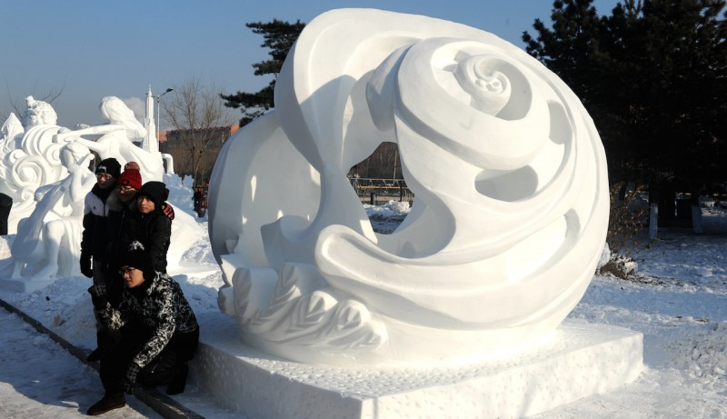 (160107) -- HARBIN, Jan. 7, 2016 (Xinhua) -- Tourists pose for photos with a snow sculpture of the 8th International Snow Sculpture Contest for College Students in Harbin, capital of northeast China's Heilongjiang Province, Jan. 7, 2016. The contest attracted 64 teams from 9 countries and regions. (Xinhua/Wang Song) (dhf)