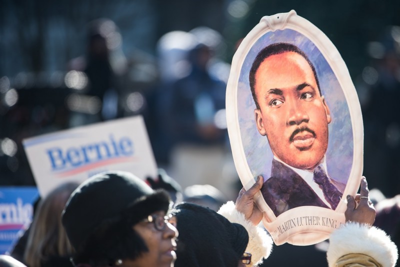 COLUMBIA, SC - JANUARY 18, 2016:   woman holds a portrait of Rev. Dr. Martin Luther King during the King Day at the Dome rally at the S.C. State House January 18, 2016 in Columbia, South Carolina. The event drew appearances from Democratic presidential candidates  Sen. Bernie Sanders, I-Vt, former Maryland Gov. Martin O'Malley and Hillary Clinton. (Photo by Sean Rayford/Getty Images)