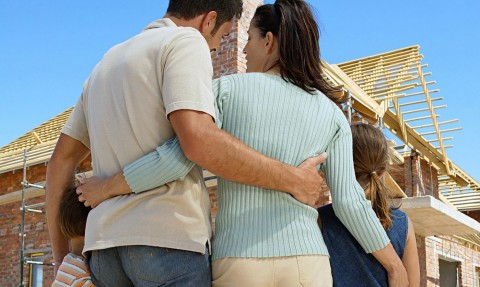 Family embracing at construction site