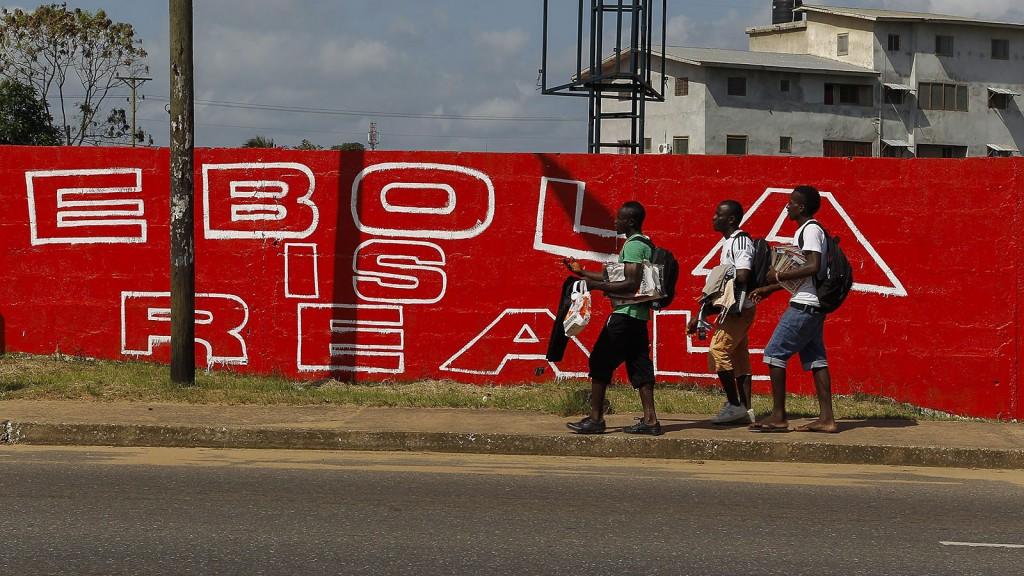 Monrovia, 2014. szeptember 8.Libériai férfiak, miután az Ebola-vírusra figyelmeztető üzenetet festettek egy falra egy figyelemfelkeltő kampány részeként Monroviában 2014. szeptember 8-án. Az Egészségügyi Világszervezet (WHO) legfrissebb információja szerint eddig 1871 megbetegedést regisztráltak Libériában, ebből 1089-en életüket vesztették. (MTI/EPA/Ahmed Jallanzo)