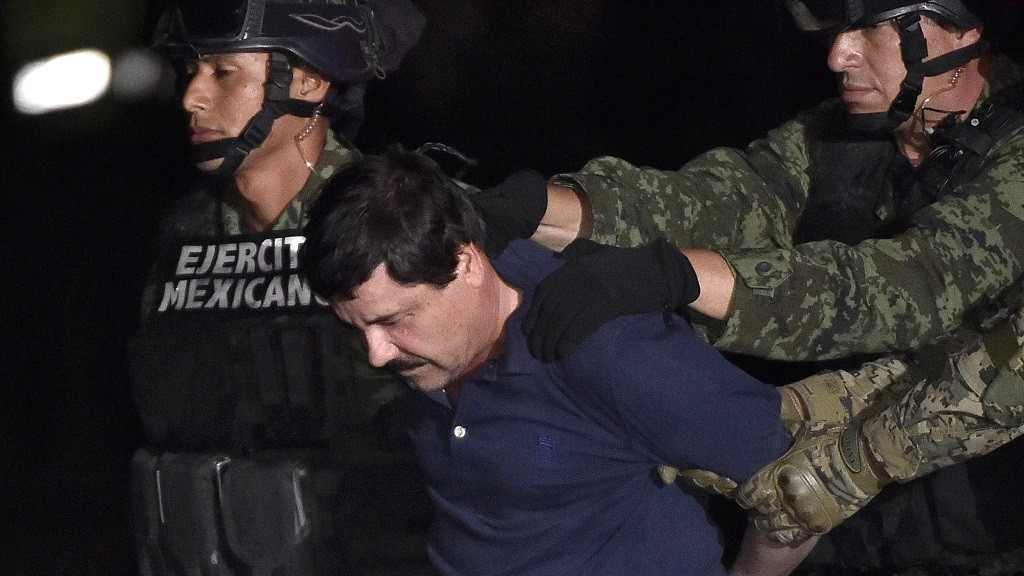 """Drug kingpin Joaquin """"El Chapo"""" Guzman is escorted into a helicopter at Mexico City's airport on January 8, 2016 following his recapture during an intense military operation in Los Mochis, in Sinaloa State. Mexican marines recaptured fugitive drug kingpin Joaquin """"El Chapo"""" Guzman on Friday in the northwest of the country, six months after his spectacular prison break embarrassed authorities.   AFP PHOTO / OMAR TORRES / AFP / OMAR TORRES"""