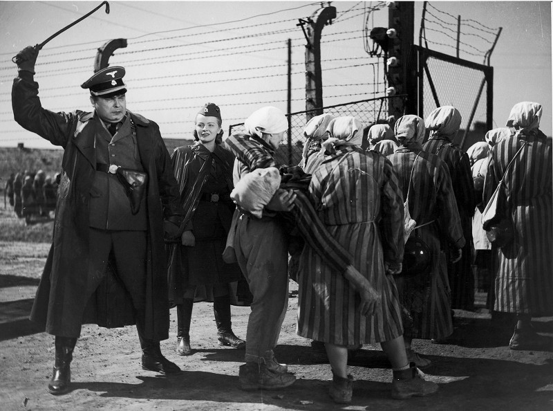 1949:  A Nazi officer raises his riding crop as a group of women carry a fellow prisoner away in a scene from Wanda Jakubowska's 'Ostatni Etap' (also known as The Last Stages or The Last Stop) which was based on her own experiences as a survivor of Auschwitz.  (Photo by Hulton Archive/Getty Images)