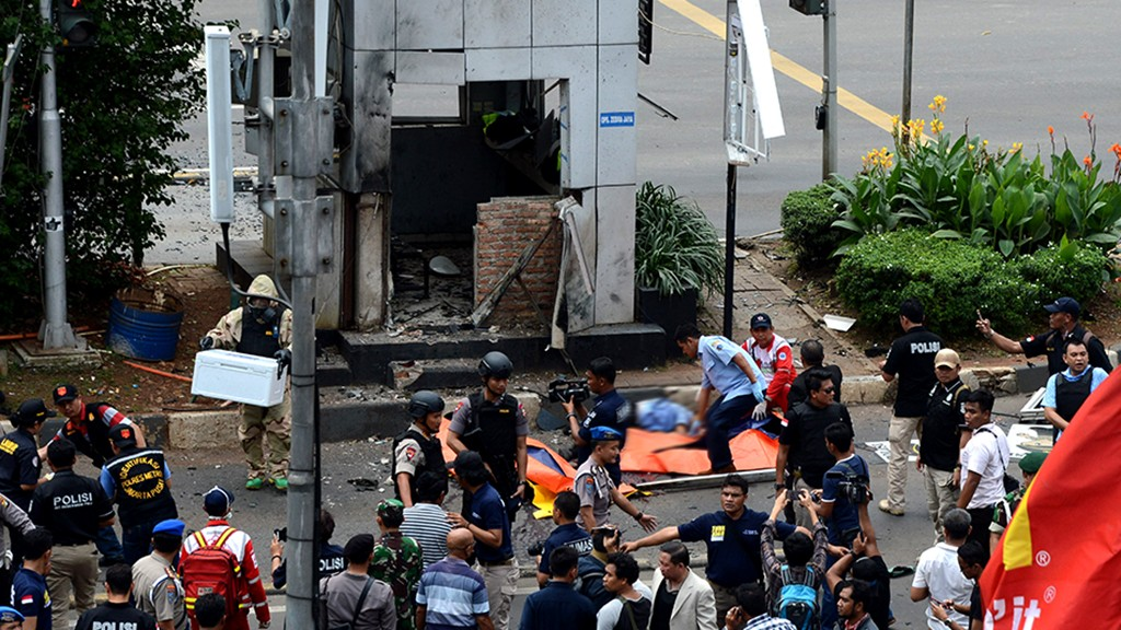 """Indonesian police secure the scene next to victims (C-in orange body bags) outside a traffic police outpost after a series of explosions hit central Jakarta on January 14, 2016.  Gunfire and explosions in the Indonesian capital Jakarta killed at least four people on January 14 in what the country's president dubbed """"acts of terror"""", with fears that militants were still on the run.     AFP PHOTO / ROMEO GACAD / AFP / ROMEO GACAD"""