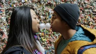 Seattle, 2015. november 11. Egy fiatal pár rágógumit fúj a Washington állambeli Seattle város híres turistalátványossága, a rágógumifal elõtt 2015. november 9-én. A város vezetése úgy döntött, hogy 20 év után ipari gépekkel, gõzöléssel megtisztítják a színes rágógumikkal kidekorált téglafalat az Egyesült Államok egyik legrégebbi piaca, a Pike Place Market történelmi falának megõrzése érdekében. (MTI/AP/Ted S. Warren)