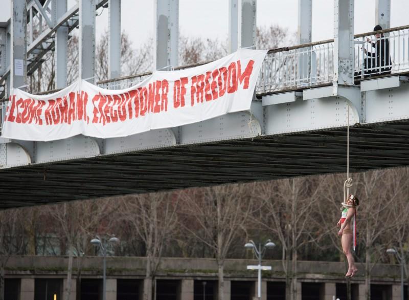 """Párizs, 2016. január 28. Kötélen lóg egy hídról Sarah Constantin, a Femen nõjogi szervezet egyik aktivistája a Haszan Róháni iráni elnök kétéves elnöksége alatt elkövetett kivégzések elleni tiltakozásként Párizsban 2016. január 28-án, Róháninak a francia fõvárosban tett látogatásával egy idõben. A hídon látható transzparens jelentése: """"Isten hozott Róháni, a szabadság hóhéra!"""". (MTI/AP/Zacharie Scheurer)"""