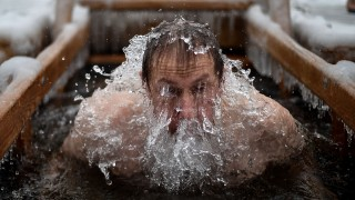 An Orthodox believer dips into the icy waters of a pond on January 19, 2016 during the celebration of the Epiphany holiday in Moscow. Among Orthodox Christians, the feast of Epiphany celebrates the day the spirit of God descended upon believers in the shape of a dove during Jesus Christ's baptism in the river Jordan. AFP PHOTO / KIRILL KUDRYAVTSEV / AFP / KIRILL KUDRYAVTSEV
