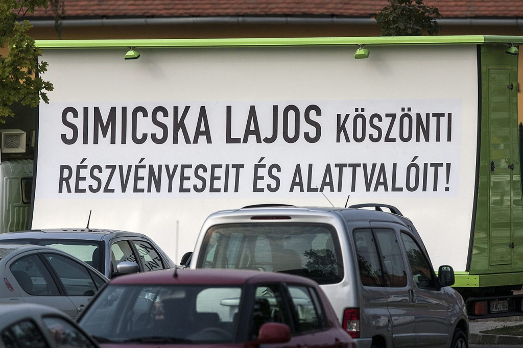 """Sárvár, 2012. szeptember 5.""""Simicska Lajos köszönti részvényeseit és alattvalóit!"""" felirat egy teherautón elhelyezett óriásplakáton a Fidesz-KDNP frakcióülésének otthont adó Park Inn Sárvár szállónál 2012. szeptember 5-én.MTI Fotó: Szigetváry Zsolt"""