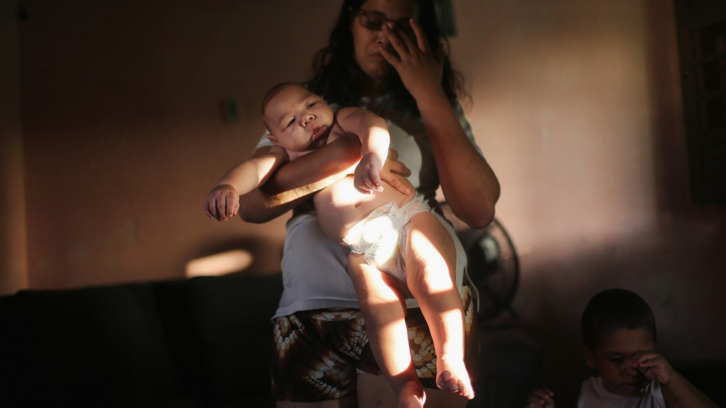 RECIFE, BRAZIL - JANUARY 25:  Mother Mylene Helena Ferreira holds her son David Henrique, 5 months, who has microcephaly, on January 25, 2016 in Recife, Brazil. In the last four months, authorities have recorded close to 4,000 cases in Brazil in which the mosquito-borne Zika virus may have led to microcephaly in infants. Microcephaly results in newborns with abnormally small heads and is associated with various disorders including decreased brain development. According to the World Health Organization (WHO), the Zika virus outbreak is likely to further spread in South, Central and North America. At least twelve cases of Zika in the United States have now been confirmed by the CDC. (Photo by Mario Tama/Getty Images)