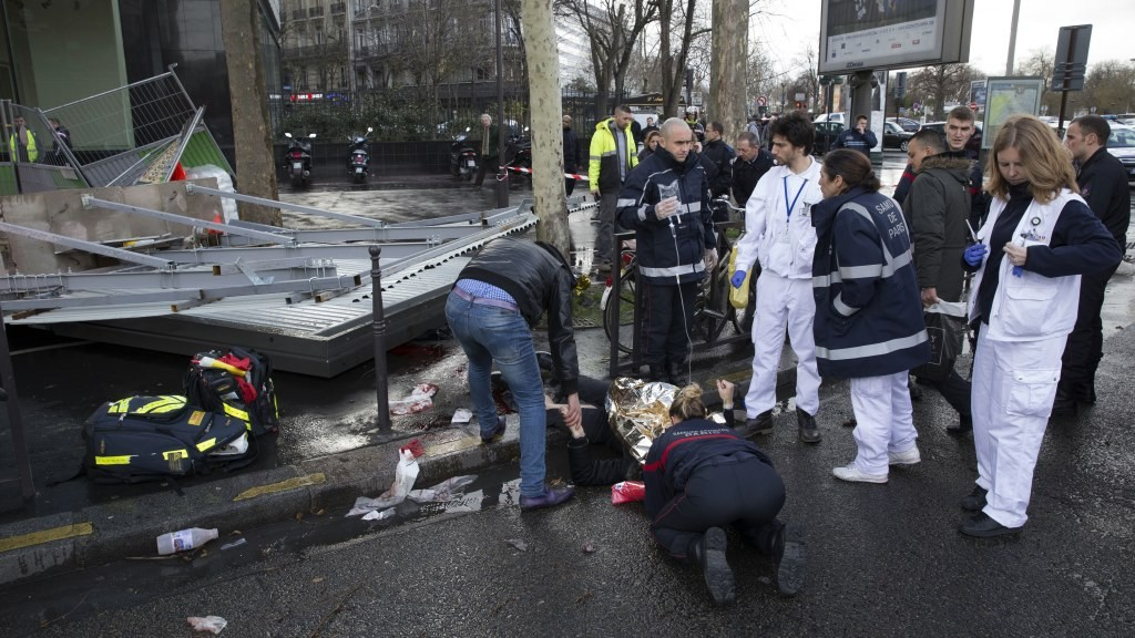 """Members of the fire brigade and emergency services administer first aid to one of the two persons injured after a billboard fell due to strong winds on February 8, 2016 in Paris. / AFP / Pompiers de Paris / Erwan Thépault / RESTRICTED TO EDITORIAL USE - MANDATORY CREDIT """"AFP PHOTO / POMPIERS DE PARIS/ ERWAN THEPAULT"""" - NO MARKETING NO ADVERTISING CAMPAIGNS - DISTRIBUTED AS A SERVICE TO CLIENTS"""