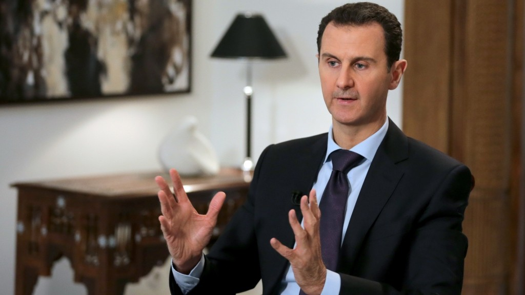 Syrian President Bashar al-Assad gestures during an exclusive interview with AFP in the capital Damascus on February 11, 2016.  / AFP / JOSEPH EID