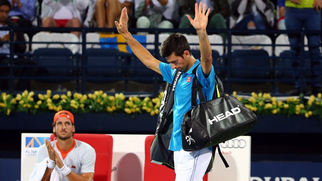 Serbian Novak Djokovic (R) gestures as he walks off the court after his withdrawal from the ATP quarterfinal tennis match against Spain's Feliciano Lopez (L) during the Dubai Duty Free Tennis Championships February 25, 2016. / AFP / MARWAN NAAMANI