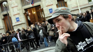 """A schoolboy smokes, 30 January 2007 outside a high school in Paris after the visit of Health and Solidarity Minister Xavier Bertrand to announce a smoking ban in public places. Smoking will be outlawed 01 February 2007 in all workplaces, hospitals, schools and shops, marking the end of the """"smokers' corner"""", as part of the French government's response to a worrying increase in cigarette consumption.  AFP PHOTO STEPHANE DE SAKUTIN   / AFP / STEPHANE DE SAKUTIN"""