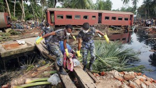 PARALIYA, SRI LANKA - DECEMBER 31:  Rescue workers continue to remove bodies from the scene of a train crash caused by the tsunami which left almost all of its 1,200 passengers dead, December 31, 2004 in Paraliya, Sri Lanka. UN Secretary General Kofi Annan, who will travel to Indonesia on January 6, warned that recovery could take up to 10 years for areas effected by the Asian tsunami. (Photo by Scott Barbour/Getty Images)