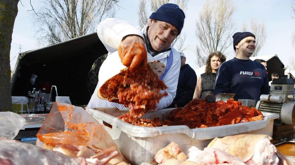 Túrkeve, 2014. február 15. Egy böllér frissen darált és fûszerezett kolbászhúst borít egy mûanyag ládába a VIII. Nemzetközi Kevi Böllértalálkozón Túrkevén 2014. február 15-én. MTI Fotó: Bugány János