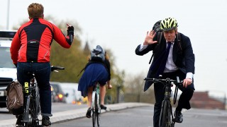 LONDON, ENGLAND - NOVEMBER 19: A cyclist makes a hand gesture to Mayor of London Boris Johnson as he cycles over Vauxhall Bridge to launch London's first cycle superhighway on November 19, 2015 in London, England. Superhighway 5 (CS5) is the capital's first two lane fully segregated cycle superhighway. (Photo by Ben Pruchnie/Getty Images)