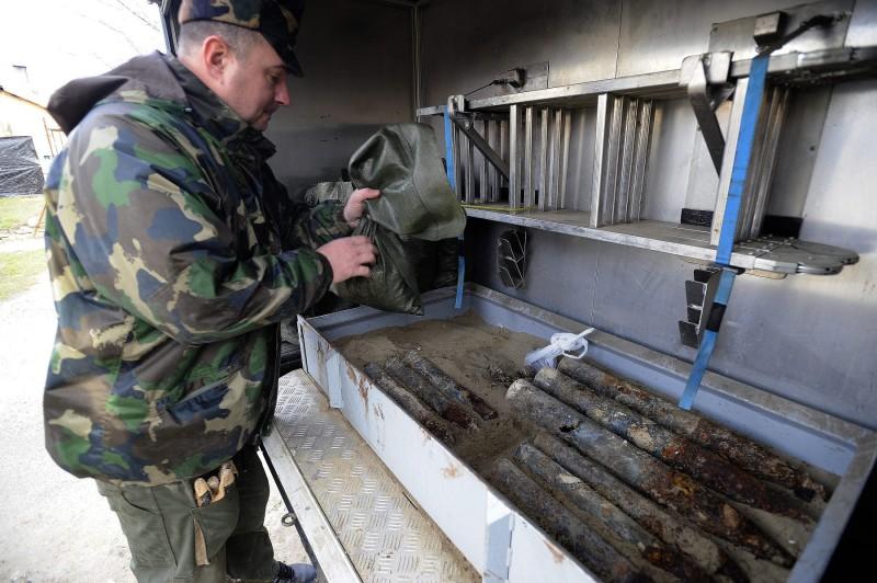 Budapest, 2016. február 27. Tûzszerész dolgozik a tûzszerészjármûben homokágyon rögzített lõszerek mellett 2016. február 27-én a XVII. kerületi Perec utcában, ahol egy építkezésen, a talajfelszínhez közel három 76 milliméteres és nyolc 45 milliméteres repeszlõszer mellett 80 kilogramm, vagyis mintegy hét zsáknyi lõport, továbbá fél kilogramm vegyes gyalogsági lõszert találtak. A tûzszerészeti munkálatok idejére tizennégy lakóház harminchat lakójának kellett elhagynia otthonát. MTI Fotó: Mihádák Zoltán