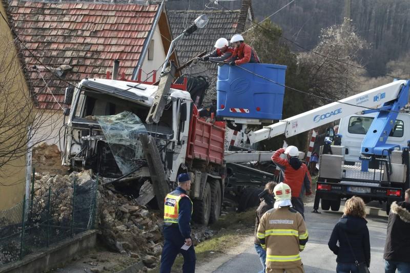 Nagyvázsony, 2016. február 9. Szakemberek dolgoznak egy összetört teherautónál a 77-es úton Nagyvázsonyban 2016. február 9-én. A tehergépkocsi eddig tisztázatlan körülmények között sodródott le az útról, majd egy gázcsonknak ütközött, kidöntött egy villanyoszlopot és letarolt egy melléképületet. A balesetben senki sem sérült meg. MTI Fotó: Nagy Lajos