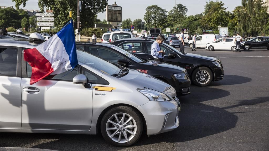 The French national flag flies from the drivers window of a Toyota Yaris Hybrid automobile as French cab drivers block traffic at Porte Maillot during protest against Uber Technologies Inc.'s car sharing service in Paris, France, on Thursday, June 25, 2015. French taxi drivers are on indefinite nationwide strike as they demand a government crackdown on what they say is Uber's use of unlicensed chauffeurs for its UberPop service. Photographer Balint Porneczi/Bloomberg