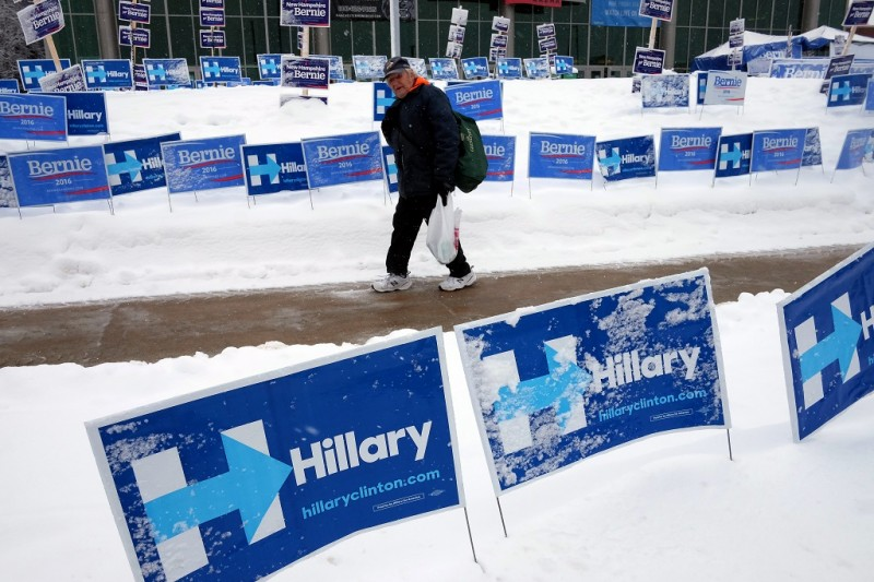 An elderly man walks past campaign posters of US Democratic presidential candidates Hillary Clinton and Bernie Sanders in Manchester, New Hampshire, on February 5, 2016.  / AFP / Jewel Samad