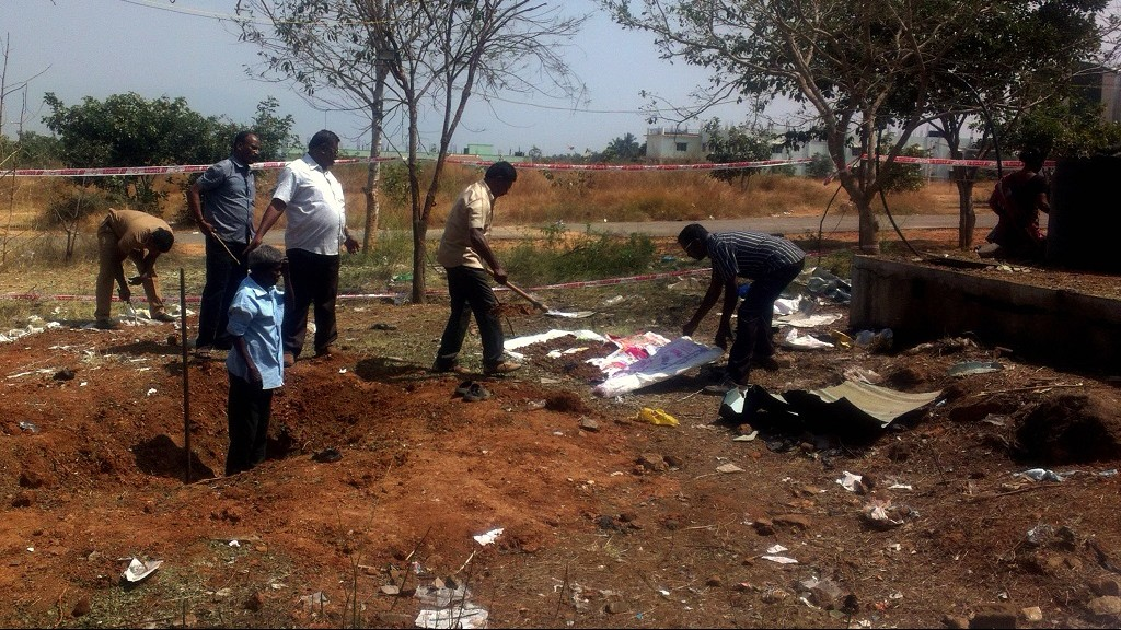 Indian authorities inspect the site of a suspected meteorite landing on February 7, 2016 in Vellore district in southern Tamil Nadu state in an impact that killed a bus driver and injured three others on February 6. If proven, it would be the first such death in recorded history. The impact of the object left a large crater in the ground and shattered window panes in a nearby building, killing the driver who was walking past.  AFP PHOTO / AFP / STR