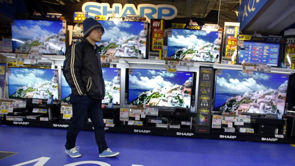 Tokió, 2016. február 25. Egy férfi megy a Sharp japán elektronikai és szórakoztatóipari óriáscég Aquos nevû televíziói elõtt egy tokiói mûszaki áruházban 2016. február 25-én. A súlyosan eladósodott Sharp ezen a napon bejelentette, hogy elfogadja a tajvani Foxconn Technology Group elektronikai beszállító vállalat egy hónappal ezelõtt tett, 600 milliárd jen (kb. 1500 milliárd Ft) értékû vételi ajánlatát. (MTI/AP/Kambajasi Sidzuo)