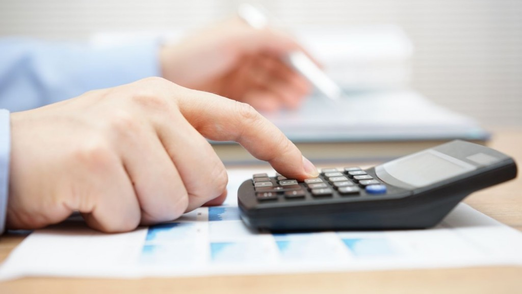 Businessman analyzing business data and using calculator