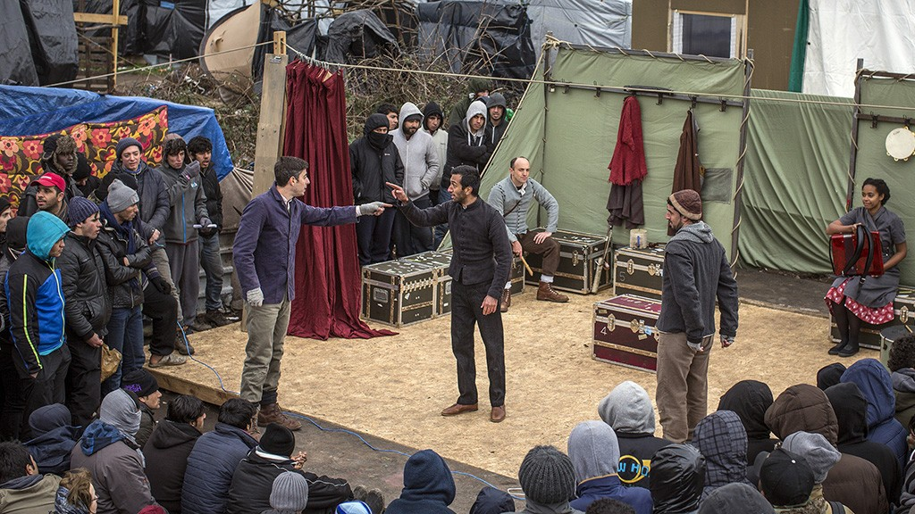 CALAIS, FRANCE - FEBRUARY 03:  Actors from Shakespeare's Globe perform Hamlet to migrants at the Good Chance Theatre Tent in the Jungle Refugee Camp on February 3, 2016 in Calais, France. The Globe to Globe tour is aiming to perform Hamlet in every country on earth over two years. They began on the 450th anniversary of Shakespeare's birth 23 April 2014, have performed in 166 countries to date and will finish at the Globe Theatre in London on the 400th anniversary of his death 23 April 2016.  (Photo by Dan Kitwood/Getty Images)