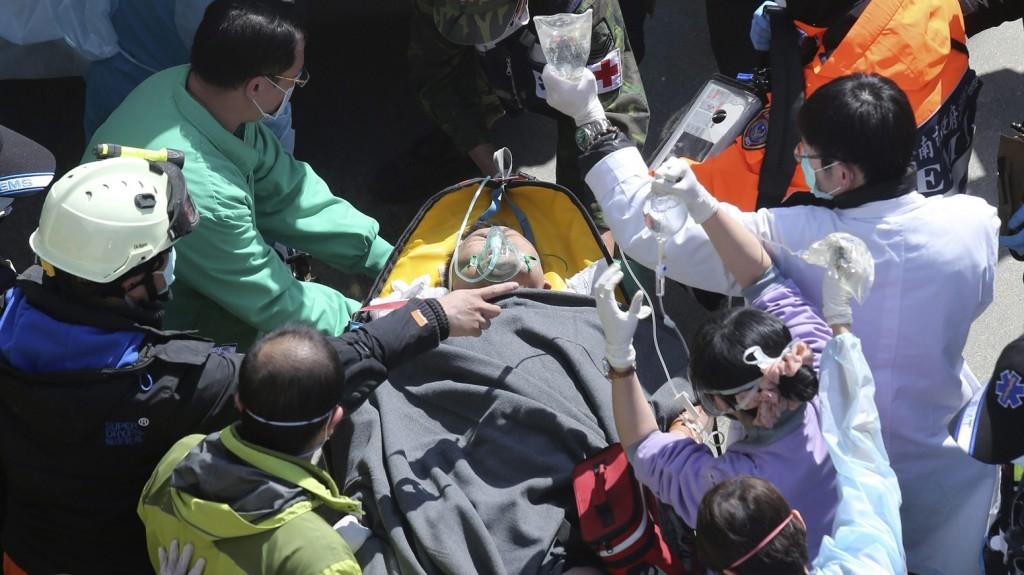 Tajnan, 2016. február 8. Mentõalakulatok tagjai egy romok közül kiemelt túlélõt visznek hordágyon a Tajvan déli részén fekvõ Tajnanban 2016. február 8-án, három nappal az után, hogy a Richter-skála szerinti 6,4 erõsségû földrengés rázta meg a térséget. A természeti katasztrófában legkevesebb 37 ember életét vesztette, több mint ötszázan megsebesültek és száztíz embert még továbbra is keresnek. (MTI/AP)