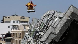 Tajnan, 2016. február 8. Mentõcsapatok tagjai daruval emelik ki egy áldozat holttestét egy 17 emeletes lakóház romjai közül a Tajvan déli részén fekvõ Tajnanban 2016. február 8-án, három nappal az után, hogy a Richter-skála szerinti 6,4 erõsségû földrengés rázta meg a térséget. A természeti katasztrófában legkevesebb 37 ember életét vesztette, több mint ötszázan megsebesültek és száztíz embert még továbbra is keresnek. (MTI/EPA/Ricthie B. Tongo)