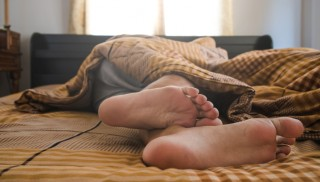 Asian man sleeping on bed under blanket, in the morning