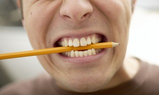 Man with pencil in clenched teeth