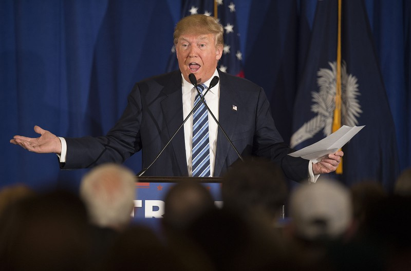 """Republican presidential candidate Donald Trump reads from a statement about Pope Francis during a campaign rally in Kiawah, South Carolina, February 17, 2016. Trump cannot claim to be a Christian, Pope Francis said Thursday, after the billionaire vowed to build a border wall to keep out immigrants. """"Anyone, whoever he is, who only wants to build walls and not bridges is not a Christian,"""" the pontiff told journalists during his return journey from a trip to Mexico in response to a question about Trump's anti-immigrant stance. / AFP / JIM WATSON"""