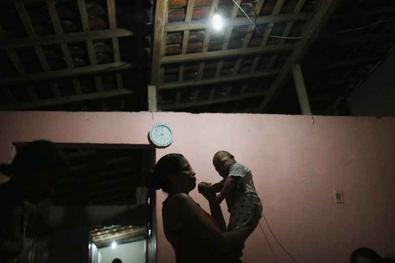 RECIFE, BRAZIL - JANUARY 29:  David Henrique Ferreira, 5 months, who was born with microcephaly, is held by her mother Mylene Helena Ferreira on January 29, 2016 in Recife, Pernambuco state, Brazil. In the last four months, authorities have recorded around 4,000 cases in Brazil in which the mosquito-borne Zika virus may have led to microcephaly in infants. The ailment results in an abnormally small head in newborns and is associated with various disorders including decreased brain development. According to the World Health Organization (WHO), the Zika virus outbreak is likely to spread throughout nearly all the Americas.  (Photo by Mario Tama/Getty Images)