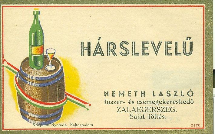 Fekvő téglalap formátumú hascímke, natúr alapon arany és piros keret, benne jobboldalon nemzeti színű szalaggal átkötött hordó, rajta egy üveg bor pohárral, jobb oldalon pedig feliratok a forgalmazóról.