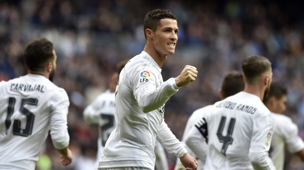 Real Madrid's Portuguese forward Cristiano Ronaldo (C) celebrates after making it a hat trick by scoring his third goal during the Spanish league football match Real Madrid CF vs RC Celta de Vigo at the Santiago Bernabeu stadium in Madrid on March 5, 2016. / AFP / GERARD JULIEN