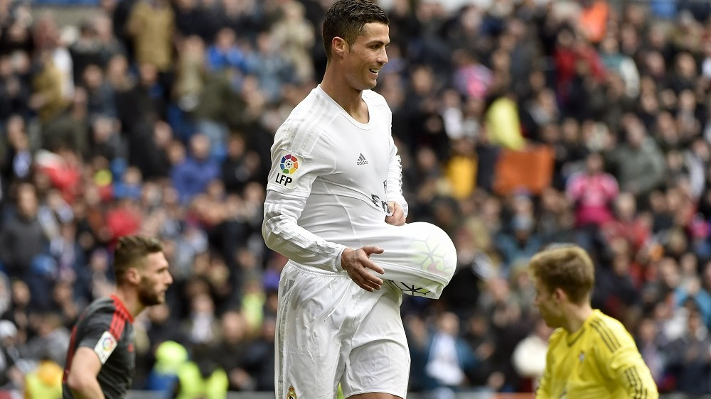 Real Madrid's Portuguese forward Cristiano Ronaldo celebrates after making it a hat trick by scoring his third goal during the Spanish league football match Real Madrid CF vs RC Celta de Vigo at the Santiago Bernabeu stadium in Madrid on March 5, 2016. / AFP / GERARD JULIEN