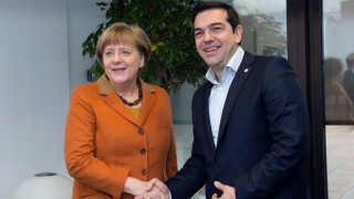 German Chancellor Angela Merkel (L) shakes hands with Greek Prime Minister Alexis Tsipras (R) during a European Union leaders' summit with Turkey on the migrants crisis at the European Council in Brussels, on March 7, 2016. EU leaders held a summit with Turkey's prime minister on March 7 in order to back closing the Balkans migrant route and urge Ankara to accept deportations of large numbers of economic migrants from overstretched Greece. The European Union is hardening its stance in a bid to defuse the worst refugee crisis since World War II by increasingly putting the onus on Turkey and EU member Greece in return for aid.  / AFP / POOL / JOHN THYS