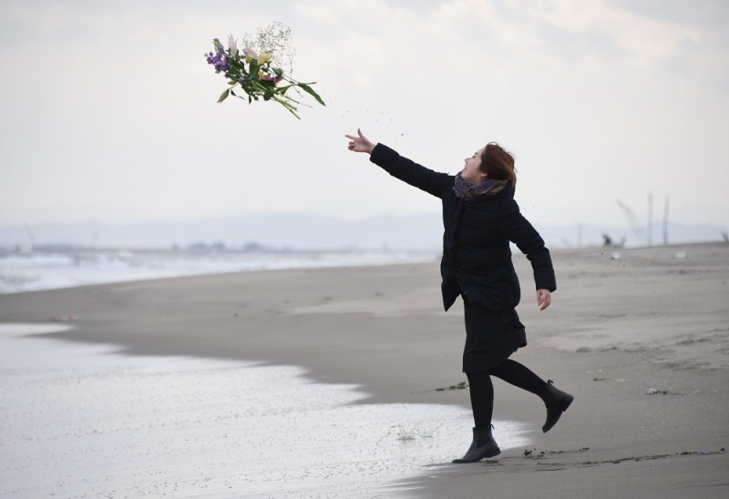 A woman throws flowers into the sea to pray for victims of the 2011 earthquake and tsunami in Sendai, northern Japan on March 11, 2016.  Japan marked the fifth anniversary of the March 11 quake and tsunami that claimed some 18,500 lives, flattened coastal communities and set off the worst atomic crisis in a generation.  / AFP / TORU YAMANAKA