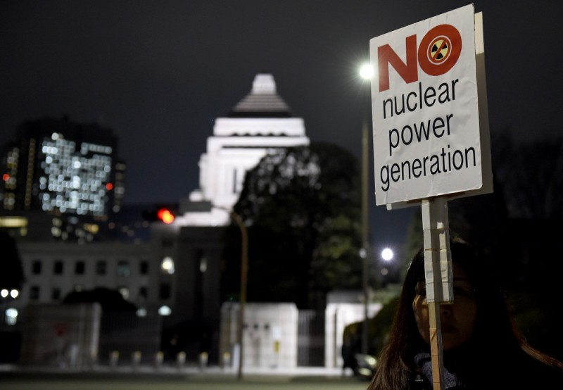 A female protester holding a placard joins an anti-nuclear demonstration rally in front of the Diet building (background) in Tokyo on March 11, 2016.   Hundreds of demonstratior staged the anti-nuclear rally on the fifth anniversary day of 2011 quake and tsunami disaster in northern Japan. / AFP / TOSHIFUMI KITAMURA