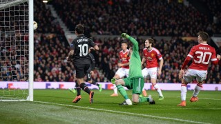 Liverpool's Brazilian midfielder Philippe Coutinho (L) shoots past Manchester United's Spanish goalkeeper David de Gea (3rd L) to score their first goal during the UEFA Europa League round of 16, second leg football match between Manchester United and Liverpool at Old Trafford in Manchester, north west England on March 17, 2016. / AFP / OLI SCARFF