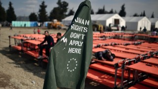 """People sit on newly arrived beds, next to a banner reading """"Human rights don't apply here"""", at the makeshift camp of the Greek-Macedonian border near the village of Idomeni on March 18,  where thousands of refugees and migrants are stranded. European Union leaders agreed late March 17, on what was described as a common position but gave no new detail about the proposals, including a key provision that Turkey provide human rights guarantees for the migrants it takes back from Greece. / AFP / LOUISA GOULIAMAKI"""